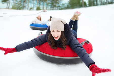 teenage girl happy: group of happy friends sliding down on snow tubes Stock Photo