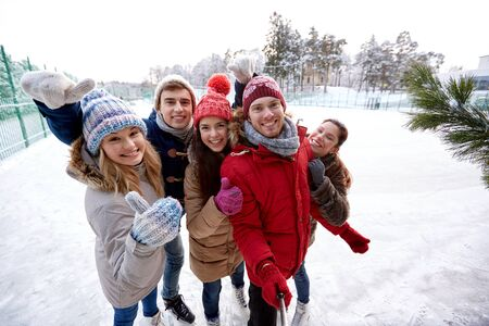 happy friends taking picture with smartphone selfie stick and showing thumbs up on ice skating rink outdoors photo