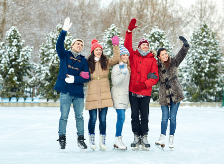 happy friends ice skating and waving hands on rink outdoors photo