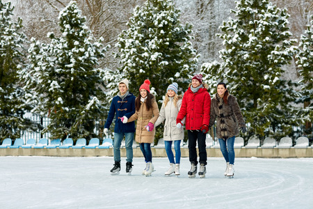 iceskates: people, winter, friendship, sport and leisure concept - happy friends ice skating on rink outdoors Stock Photo
