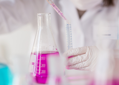 female scientist: close up of young female scientist with pipette and flask making test or research in clinical laboratory