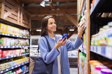 chicas comprando: venta, compras, consumismo y el concepto de la gente - mujer joven feliz con el teléfono inteligente elegir y comprar alimentos en el mercado