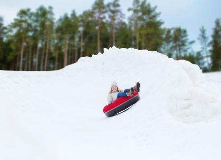 jeune fille: heureuse fille ou une femme adolescente glisser vers le bas sur le tube de neige Banque d'images