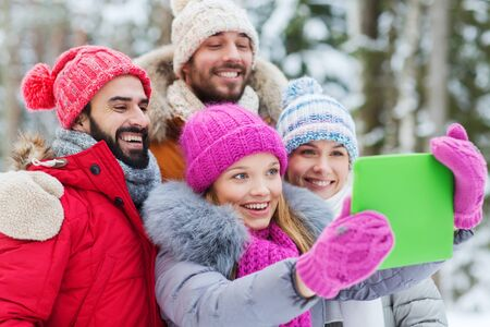 tablet: group of smiling men and women taking selfie tablet pc computer in winter forest