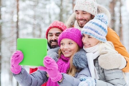 group of smiling men and women taking selfie tablet pc computer in winter forest photo