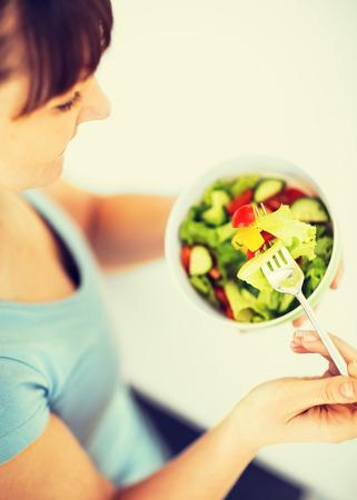 Comida sana y concepto de cocina - mujer que come ensalada con verduras Foto de archivo - 36972534