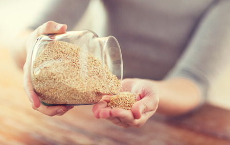 close up of female emptying jar with quinoa