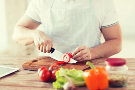 hombre cocinando: Close up de tomate de corte masculino mano en la tabla de cortar con cuchillo afilado
