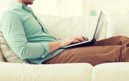 ラップトップ コンピューターで作業と自宅のソファに座っている男のクローズ アップ