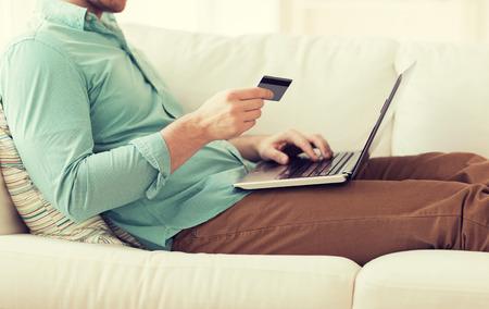 orden de compra: Cerca del hombre con el ordenador portátil y tarjeta de crédito en casa