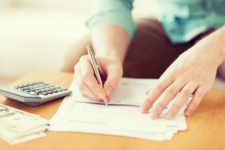 close up of man with calculator counting money and making notes at home