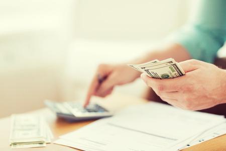 efectivo: Cerca del hombre con la calculadora contar dinero y haciendo notas en casa