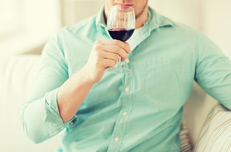 degustating: close up of man drinking red wine and sitting on couch at home