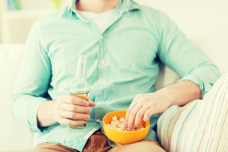 snack time: close up of man with popcorn and beer sitting on couch at home