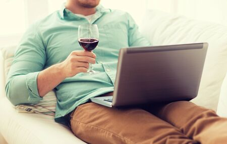 chilling: close up of man close up of man with laptop and glass of wine at home Stock Photo
