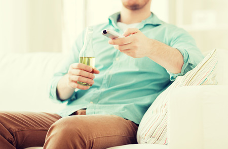 nonalcoholic beer: man changing tv channels and drinking beer at home Stock Photo