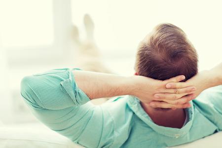 relajado: hombre acostado o sentado en el sofá en casa de atrás Foto de archivo