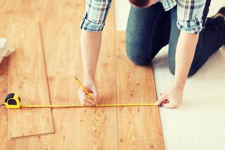 木製のフロアー リングを測定する男性の手のクローズ アップ