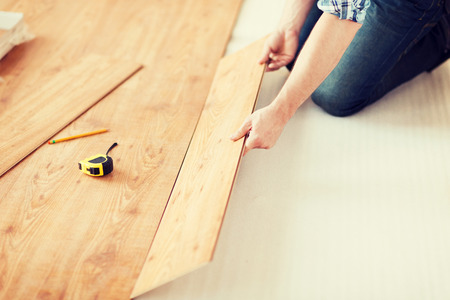 close up of male hands installing wood flooring