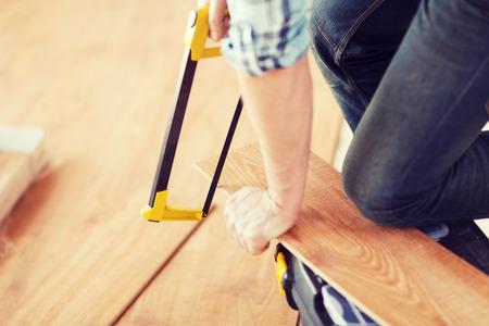 materiales de construccion: close up de manos masculinas corte tabla de piso de parquet con una sierra Foto de archivo