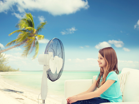 girl blowing: smiling little girl sitting on sofa with big fan at home