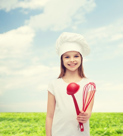 smiling little girl in cook hat with ladle and whisk photo