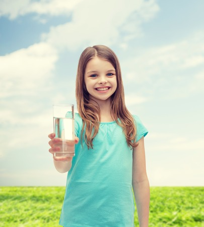 preteen  pure: smiling little girl giving glass of water Stock Photo