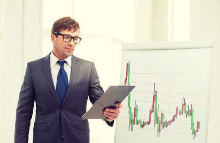 businessman in suit and black eyeglasses with clipboard and flip board with forex chart in office photo