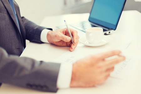 audit: close up of man hands with contract and pen, coffee and laptop computer Stock Photo