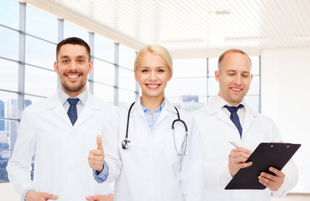 group of doctors with stethoscope and clipboard showing thumbs up over clinic background photo