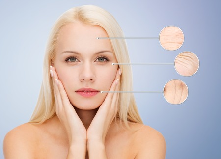 aging woman: people, skin care and beauty concept - face of beautiful happy young woman over blue background
