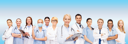 doctors smiling: healthcare and medicine concept - smiling female doctors and nurses with stethoscope Stock Photo
