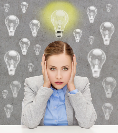 hands covering ears: business, education, emotional pressure and people concept - stressed businesswoman or student covering her ears with hands over concrete background with light bulbs