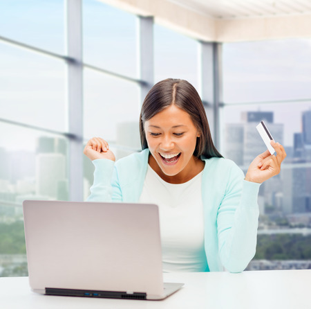 asian shopper: online shopping, banking, business and people concept - happy businesswoman with laptop and credit card over office window background