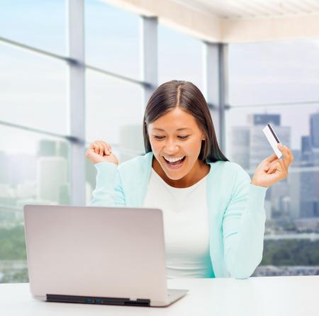 online winkelen, bankieren, zakelijke en mensen concept - gelukkig zakenvrouw met een laptop en een creditcard op loket achtergrond