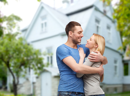 nice accommodations: love, people, real estate, home and family concept - smiling couple hugging over house background