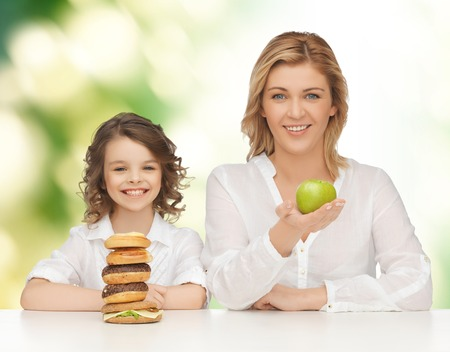 people, healthy lifestyle, family and unhealthy food concept - happy mother and daughter eating different food over green background photo