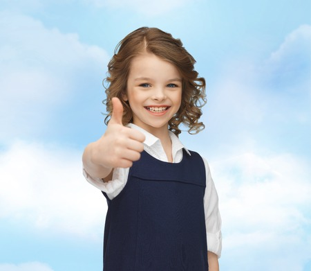 pre approval: people, gesture, children, summer vacation and happiness concept happy little school girl showing thumbs up blue sky background Stock Photo