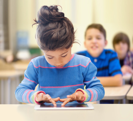 education, elementary school, technology and children concept - little student girl with tablet pc over classroom and classmates background photo