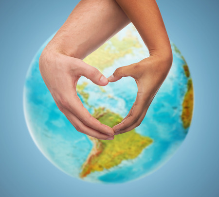 world peace: people, peace, love, life and environmental concept - close up of human hands showing heart shape gesture over earth globe and blue background