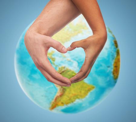 Pessoas, paz, amor, vida e conceito ambiental - close-up de mãos humanas, mostrando o gesto de forma de coração sobre o globo da terra e fundo azul Foto de archivo - 37056190