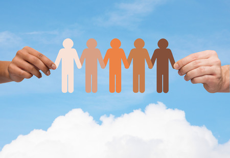 tolerancia: comunidad, la unidad, la gente y el apoyo concepto - par de manos que sostienen la cadena de papel personas multirraciales sobre el cielo azul y nubes de fondo Foto de archivo