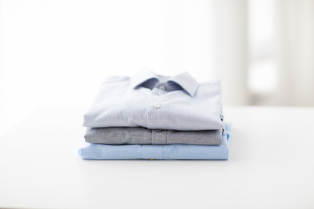 ironing, laundry, clothes, housekeeping and objects concept - close up of ironed and folded shirts on table at home Stock Photo