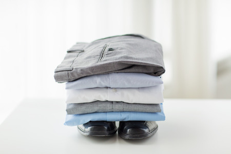 business, clothes, housekeeping and objects concept - close up of ironed and folded shirts, trousers and formal shoes on table at home