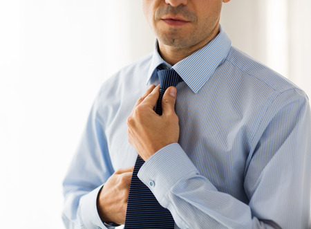 necktie: people, business, fashion and clothing concept - close up of man in shirt dressing up and adjusting tie on neck at home