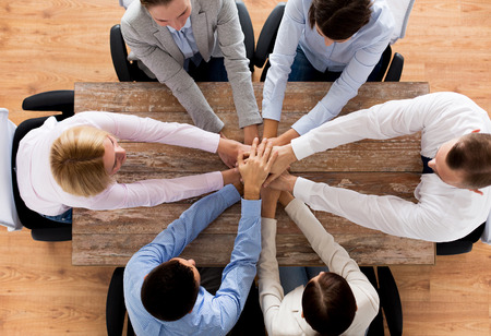 business, people, cooperation and team work concept - close up of creative team sitting at table and holding hands on top of each other in office Archivio Fotografico