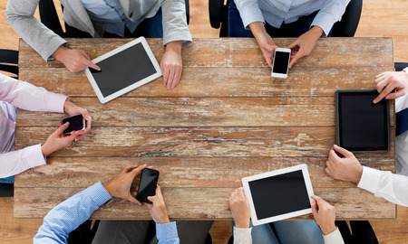 mobile telephones: business, people, technology and team work concept - close up of creative team with smartphones and tablet pc computers sitting at table in office
