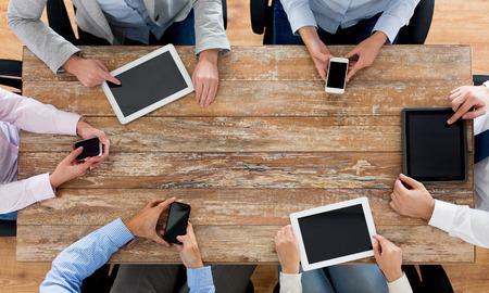 colaboracion: negocio, la gente, la tecnolog�a y el trabajo en equipo concepto - cerca de equipo creativo con los tel�fonos inteligentes y computadoras tablet pc sentado a la mesa en la oficina Foto de archivo