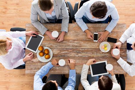 bedrijfsleven, mensen, pauze en teamwork concept - close-up van het creatieve team vergadering en het drinken koffie met muffins tijdens de lunch in het kantoor