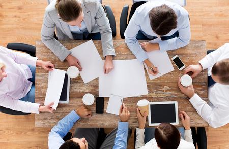 bedrijfsleven, mensen en teamwerk concept - close-up van het creatieve team met papieren en gadgets vergader- en drinken koffie in het kantoor Stockfoto